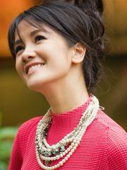 Hình ảnh ca sĩ Hồng Nhung cao quý với vòng ngọc trai trên nền áo màu đỏ tinh tế, nổi bật, vẫn với phong cách trẻ trung, nhí nhảnh của cô ca sĩ không tuổi