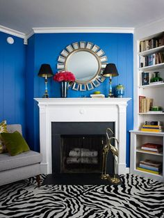 Living room with royal blue walls, grey sofa, white fireplace with a sunburst mirror on the mantel, built in bookshelves and zebra print car...