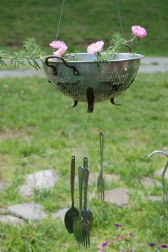 Vintage aluminum colander windchime with flowers planted in the top.