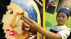 Yuka Takahashi, 9, attaches the last piece of Lego brick to a replica of Johannes Vermeer's 'Girl with a Pearl Earring' at the Legoland Discovery Center Tokyo on August 9.
