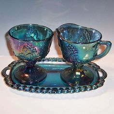 This iridescent blue Carnival Glass is in the Harvest Grape design by Indiana Glass. This set includes;  a creamer, open sugar, and small tray.  All