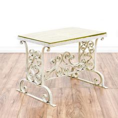This cottage chic end table is featured in a wrought iron with an off white patina finish. This side table has a durable glass table top, curved swirl accents and a trestle stretcher base. Perfect for an outdoor patio! #cottagechic #tables #diningtable #sandiegovintage #vintagefurniture