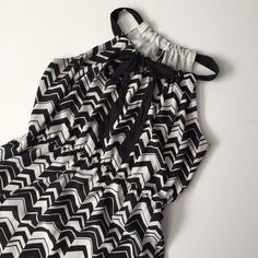 "Black and White Chevron Dress Cute and Classy black & white chevron pattern dress!! Good condition! Under arms have slightly gray hue but not noticeable when wearing. Neckline is super fun and can be cinched to change the width of the chevron fabric or to cover more of the neckline. Black neck tie can also be undone and styles however you like. Has a cinched elastic waist. Length about 35"", pit to pit 20"", waist 32"" unstretched (41"" stretched). Dress is lined! 100% polyester. NO TRADES…"