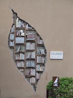 sculpture on the outside walls of the Community Library in Monzuno, Italy .... looks like hole in wall revealing books on shelves