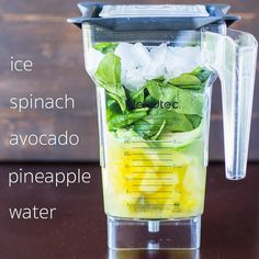 A photo of a blendtec blender with pineapple, spinach, avocado, pineapple, ice and water. The ingredients are written in white, and it is against a dark wood background.