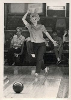Vintage black and white photo of a young lady bowling in the 60's sporting a bouffant flip hairstyle.