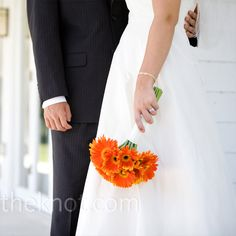The couple's florist made Erin's wedding bouquet entirely out of orange gerbera daisies -- her favorite flower.