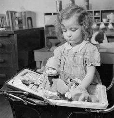 Object description Jacqueline (aged 3) is an evacuee from Luxembourg to Surrey. Here we see her playing with her doll and doll's pram at the house in which she is staying, somewhere in Surrey c.1942