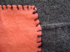 Hand stitched & repurposed charcoal gray cashmere blanket with salmon cashmere detail.