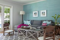 "Jackson Paige Interiors designed this Brentwood home with a contemporary approach but added touches of coastal style throughout the space. This family room, for example, features a soft turquoise wallpaper as an accent wall, complementary sofa pillows, along with a coffee table, end table and art that inspire one to ""hit the beach."" Especially fetching are the low-to-the-ground occasional chairs that have a cottage-style aesthetic."