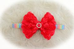 Colorful and fun, this multi-colored, chevron elastic band is attached to a hot pink, rosette bow with a rhinestone slider in the middle.
