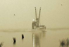 Shrimp boat returning to harbor on foggy evening. Art photography.