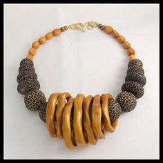 Bold and dramatic necklace....and one of a kind! Old handmade Mail clay beads are woven thru handmade metallic gold clay freeform rings. The rings actually can be removed from necklace by simply sliding them off.....for a totally different look.....its like getting 2 necklaces
