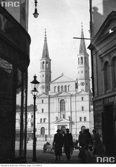 Fragment zachodniej pierzei Starego Rynku z kościołem. Na przodzie widoczni przechodnie, z boku latarnia uliczna.