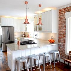 GORGEOUS white kitchen next to brick wall........ Pendant lamps are IKEA hack- spray painted copper.....!!