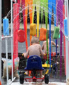 "Homemade car wash (Parenting Magazine) - hang strips of vinyl table cloths and colorful sponges from PVC piping. Direct sprinklers to ""wash"" the kids on scooters/trikes/wagons."