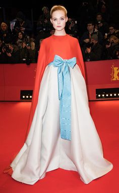 ELLE FANNING wears a Valentino Couture gown with a dramatic red cape and pale blue bow around the waist to the Berlin Film Festival's Opening Ceremony and premiere of Isle of Dogs in Berlin.