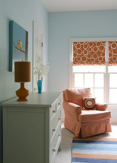 Sweet blue & orange blue nursery design with blue walls paint color, orange geometric pattern fabric roman shades, orange glider with turquoise blue piping, orange & blue striped rug, gray chest and orange lamp.