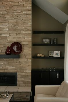 Stacked stone fireplace with chunky wood floating mantle shelf and linear fireplace. Floating shelves on the side with cabinets below.