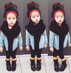 Cute little girl with a messy bun, and a headband. Jeans jacket and black scarf with black pants and boots