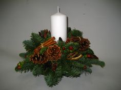 Small round table centre with a single white pillar with berries, cones, cinnamon sticks and dried fruit slices. Christmas Flowers, Christmas Wreaths, Christmas Arrangements, Table Centers, Dried Fruit, Cinnamon Sticks, Candle Sconces, Centre, Berries