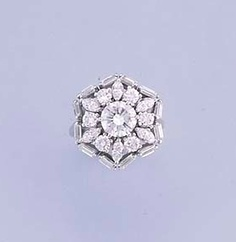 A DIAMOND CLUSTER RING   Of openwork design, the central brilliant-cut diamond weighing 1.12 carats within brilliant and marquise-cut diamond surround to the baguette-cut diamond angular border and fluted hoop