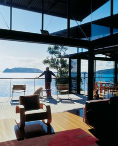 The owner of a hillside home overlooking Australia's Pittwater Bay takes in a panoramic view of the ocean from his balcony.