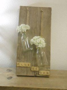 Geweldig leuk idee, geplukt van facebook: vaasjes via touwtjes bevestigen aan een houten plank en vullen met een mooie bloem.