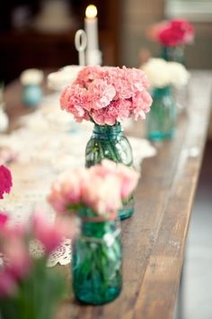 Mix pink carnations with polo roses and greenery in table centerpieces