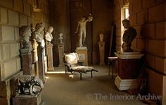 Houghton Hall ~ A bath chair surrounded by classical busts and statues