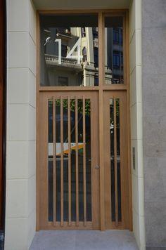 Puerta de madera de Iroko diseñada por Monente Arquitectura para un edificio en sus obras de rehabilitación de fachada, cubierta y adaptación a la accesibilidad con instalación de ascensor.