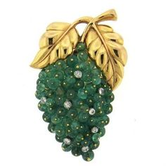 An 18k gold brooch by Gazdar set with emeralds and approximately 0.24ctw of G/VS diamonds. (*some emeralds have slight chips - visible upon close inspection*). DESIGNER: Gazdar MATERIAL: 18K Gold GEMS