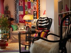 Textile-rich living room. Comfortable sofas and chairs, cushions, throws, curtains and bookshelves for displaying treasures bring an exotic feel to this living room.