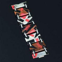 Jean Dunand 。.   Bracelet manchette (c. 1930) à six plaques rectangulaires articulées, exécutées en métal argenté et en bois, montées en alternance, lune servant de fermoir en demi-plaque à deux goupilles. Décor de motifs géométriques laqués, noir et rouge sur fond uni argent ou en palissandre (usures de surface et légères rayures).