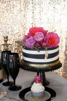 Black and white striped wedding cake with gold accents and pink flowers.