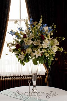 . White, pale blue and red flowers: lilies, roses,  ammi, lisianthus, delphinium, dahlias. Impresive table arrangement for the high ceiling reception room.