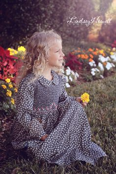 Beautiful fall smocked girls dress with long sleeves, floral fabric in dark blue color and pink hand embroidered roses.