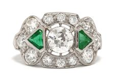 The McKinney Art Deco diamond and emerald three stone engagement ring. Centered by a captivatingly brilliant 1 carat old European diamond flanked by a pair of lush, vivid green emerald triangles. As if that wasn't enough, this 1920s Jazz Age heirloom is accented with a dozen dazzling round diamonds to complete this trinity band. #artdeco #diamond #emerald #platinum #trinity #trinityring #3stonering #3stonerings #engagementring #engagementrings #oldeuropeandiamond #oldeuropeandiamonds #love…