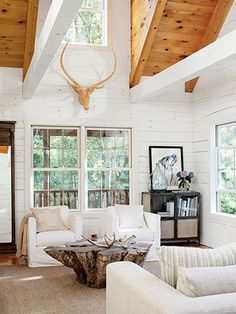 Quirky finds—a coffee table forged from a centuries-old tree trunk and a carved-wood faux deer head—bring personality and warmth to this Ohio lake house's living room.