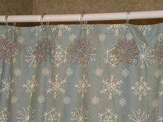 Decorate the bathroom for the holidays by hanging snowflake ornaments on shower curtain