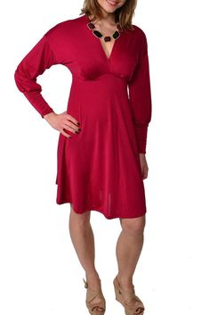This lovely empire dress by 24/7 Comfort Apparel features a faux wrapped effect at the bodice, creating a feminine V-neck for a sensual but classy look. Slight stretch in construction, an empire waist, and long gradually fitted sleeves give this knee-length dress a flattering, comfortable fit for body type. Easily dressed up or down, this versatile piece is perfect in any wardrobe.        V-neckline, elastic empire waist, knee-length, empire dress, long sleeves. Faux wrapped bodice  …