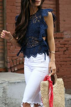 Distressed white jeans with semi sheer lace navy blue blouse, red scarf tied on purse handle