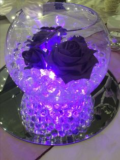 Fish bowl wedding centrepiece for purple themed weddings.  Purple illuminated beads, cadburys purple roses and Ivory butterfly. Available to hire for your wedding in Swansea, Neath, port talbot, Bridgend, porthcawl, Llanelli, Carmarthen and surrounding areas of South Wales from affinity event decorators http://www.affinityeventdecorators.com
