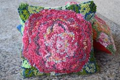 Floral rug hooked pillow by Deanne Fitzpatrick. Pink hued rose with green touches. Interior design.