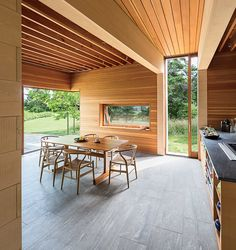 Douglas fir and Alaskan cedar richly line the interior walls, and the flooring is made of Vermont slate. In the kitchen and dining area, a group of Wishbone chairs by Hans Wegner for Carl Hansen & Søn surrounds a table by local furniture maker Larry Heple Interior Architecture, Interior Design, Interior Walls, Tropical Architecture, Slate Flooring, Prefab Homes, A Table, Concrete, House Design