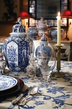 Blue and white tablecloth, delft, china, silverware and candlesticks, red lampshades - Charlotte Moss
