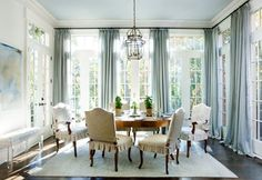 such an amazing dining room. i love the windows and drapes that are as high as the ceiling and go to the floor.