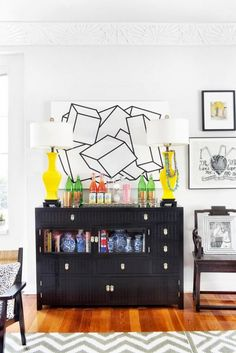 Elegant living space with monochrome art. bright yellow lamps, and a bar cart