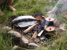 Salmons and stews cooking by a fire in the Iron Age village in the Land of Legends, Denmark