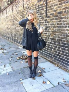 black loose short dress with gray sweater over and black lace up combat boots with sheer black over the knee high hose.